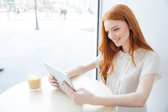Smiling  woman sitting and using tablet in cafe Royalty Free Stock Photography