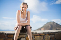 Smiling woman sitting on wall Stock Photography