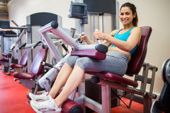 Smiling woman sitting in the weights machine Royalty Free Stock Photo