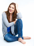 Smiling woman sitting on a white floor. Royalty Free Stock Photography