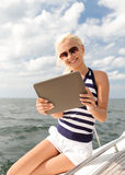 Smiling woman sitting on yacht with tablet pc Royalty Free Stock Images