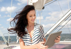 Smiling woman sitting on yacht with tablet pc Stock Photography