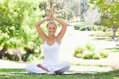Smiling woman sitting in a yoga position outdoors Stock Photo