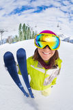 Smiling woman in ski mask close-up view from up. Smiling woman in ski mask holds ski view from up and snow mountains on background in Sochi Royalty Free Stock Image