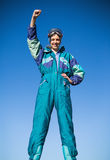 Smiling woman in ski suit putting hand up Stock Photos