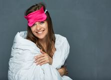 Smiling woman with sleep mask wearing white blanket. Healthy sleep concept isolated in studio Royalty Free Stock Photography