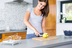 Smiling woman slicing apple. On kitchen Stock Photography