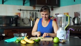 Smiling Woman Slicing Avocado in the Kitchen. Smiling Woman Slicing Fresh Avocado on a Cutting Board in the Kitchen in Slow Motion. Making a Smoothie Process stock video