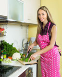 Smiling woman slicing green pepper Stock Photography