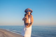 Smiling woman with a small dog. Smiling woman in a funny sunglasses with a small dog in her arms is posing on deserted beach during sunset and having fun. Happy Stock Photos