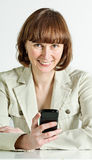 Smiling woman with smartphone. Smiling middle aged woman sitting at an office desk and holding smarphone Royalty Free Stock Photography