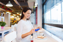 Smiling woman with smartphone and coffee at cafe Royalty Free Stock Image