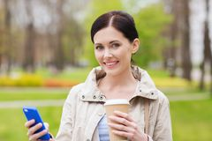 Smiling woman with smartphone and coffee in park Royalty Free Stock Photos
