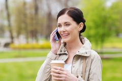 Smiling woman with smartphone and coffee in park Stock Image