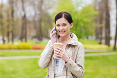 Smiling woman with smartphone and coffee in park Royalty Free Stock Photo