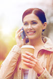 Smiling woman with smartphone and coffee in park Royalty Free Stock Photography