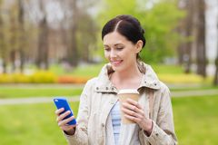 Smiling woman with smartphone and coffee in park Stock Photos