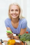 Smiling woman with smartphone cooking vegetables Royalty Free Stock Photography