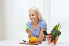Smiling woman with smartphone cooking vegetables Royalty Free Stock Photos