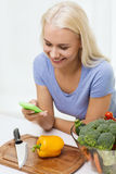 Smiling woman with smartphone cooking vegetables Royalty Free Stock Images