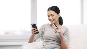 Smiling woman with smartphone and credit card stock footage