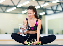 Smiling woman with smartphone and earphones in gym Stock Image