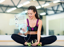 Smiling woman with smartphone and earphones in gym Stock Photo
