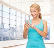 Smiling woman with smartphone in gym Stock Photo