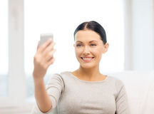 Smiling woman with smartphone at home Stock Images