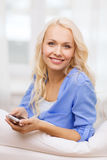 Smiling woman with smartphone at home. Home, technology and internet concept - smiling woman with smartphone lying on couch at home stock photo