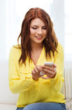 Smiling woman with smartphone at home Royalty Free Stock Photography