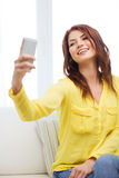 Smiling woman with smartphone at home Stock Image