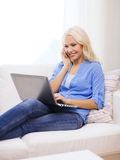 Smiling woman with smartphone and laptop at home. Home, technology and internet concept - smiling woman with smartphone and laptop computer sitting on couch at Royalty Free Stock Photos
