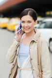 Smiling woman with smartphone over taxi in city Royalty Free Stock Image