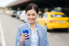 Smiling woman with smartphone over taxi in city Stock Image