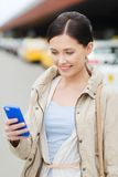 Smiling woman with smartphone over taxi in city Stock Images
