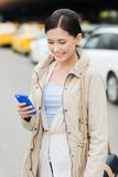 Smiling woman with smartphone over taxi in city Stock Photography