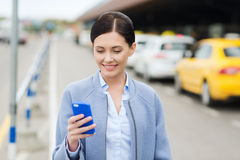 Smiling woman with smartphone over taxi in city. Travel, business trip, people and tourism concept - smiling young woman with smartphone over taxi station or royalty free stock photo