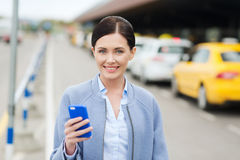 Smiling woman with smartphone over taxi in city Stock Photo