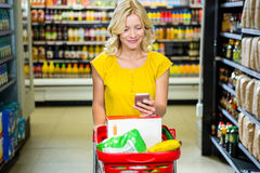 Smiling woman with smartphone pushing trolley in aisle Royalty Free Stock Photo