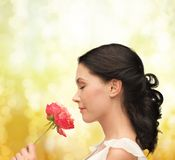 Smiling woman smelling flower Stock Image