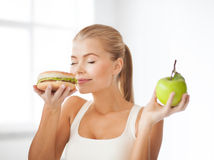 Smiling woman smelling hamburger and holding apple Royalty Free Stock Image