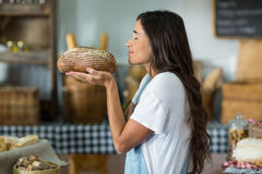 Smiling woman smelling a round loaf of bread at counter Royalty Free Stock Photography