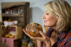 Smiling woman smelling a round loaf of bread at counter Royalty Free Stock Photo