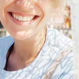 Smiling woman with smooth healthy smile on sunny street close-up stock image