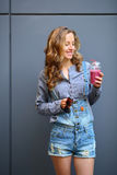 Smiling woman with a smoothie in disposable cup in their hands Stock Images