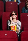 Smiling woman with a snack. In the 3D movie Stock Image