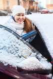 Smiling woman with snow brush and snowy car Royalty Free Stock Photo