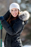 Smiling woman with snow shovel. A cute woman smiles and fixes her hat while holding a snow shovel Stock Images