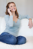 Smiling woman on the sofa answering the phone Royalty Free Stock Images